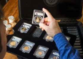 Man inspecting his collection of certified gold and silver coins in slab cases