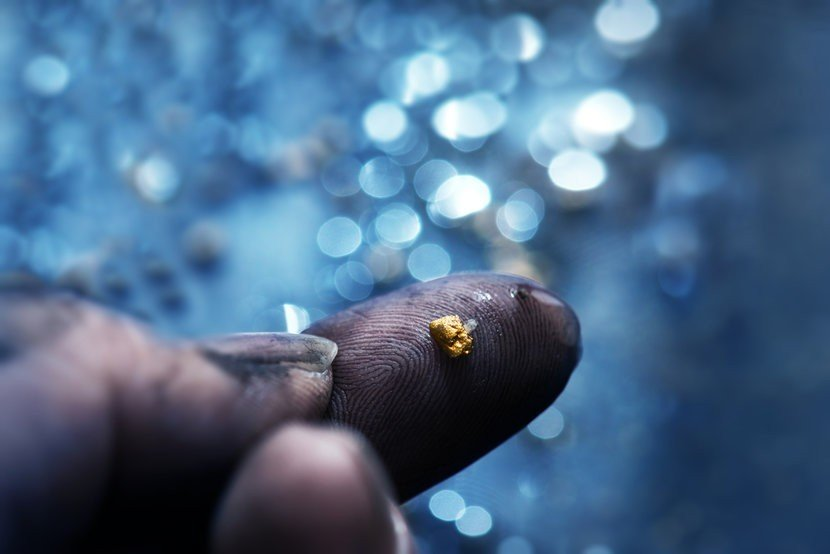Tiny nugget of freshly mined gold on dirty pointer finger