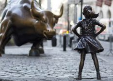bronze statue of the back of a confident little girl straing directly into the eyes of the bronze wall street journal bull
