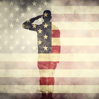 outline of soldier saluting on an American flag background
