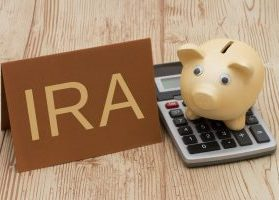 Gold piggy bank sitting on top of calculator and sign reading IRA