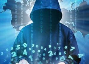 Man in black hoodie typing on keyboard with lines of code overlaid opaquely on him