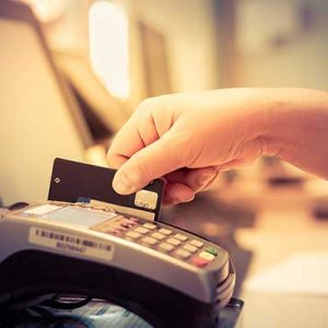 hand swiping credit card through credit card machine