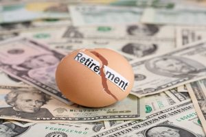 "Broken egg that says, ""Retirement"" on top of U.S. dollar bills"
