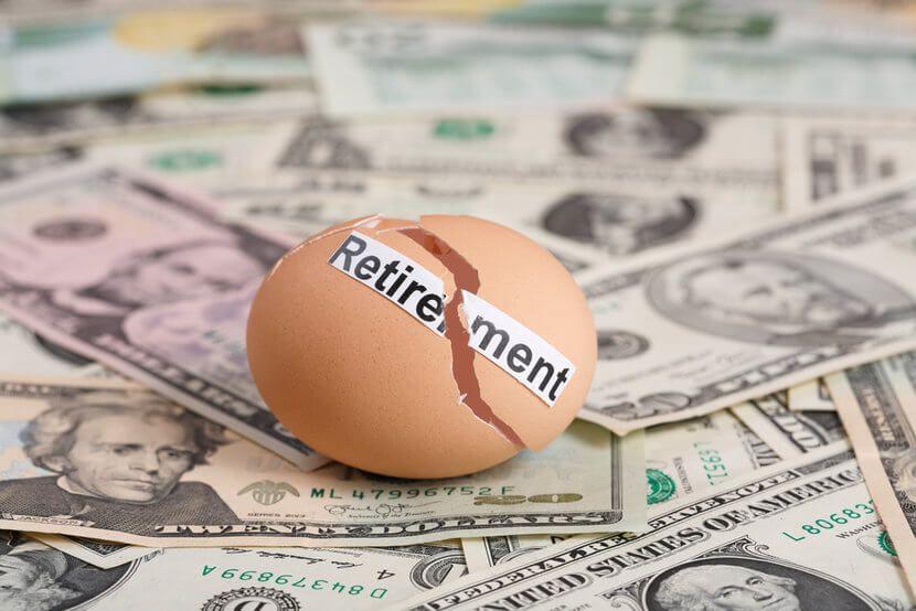 """Broken egg that says, """"Retirement"""" on top of U.S. dollar bills"""