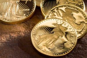 Proof Gold American Eagles displayed on wooden table