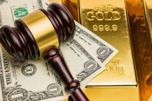 Courtroom gavel, U.S. dollar bills, and shiny gold bars