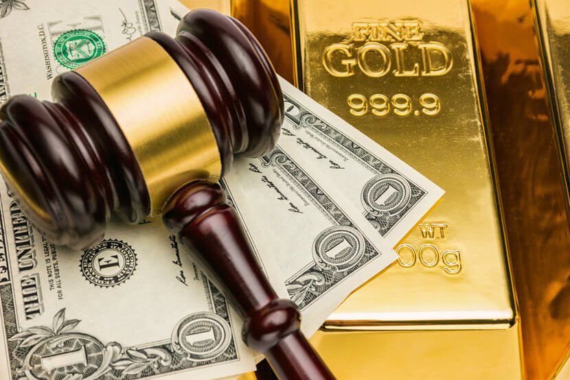 Courtroom gavel, U.S. dollar bills, and shiny gold bars
