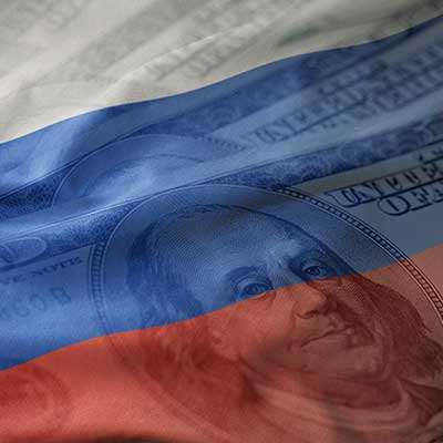 U.S. one hundred dollar bill faded into the Russian flag