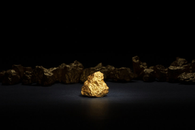 Small nugget of gold on black background