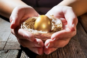 Hands holding nest with golden egg inside