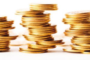 Three stacks of shimmering, teetering gold coins