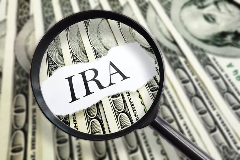 Magnifying glass hovering over IRA on top of U.S. dollars