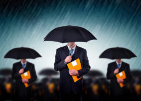 Businessmen with umbrella standing in stormy rain.