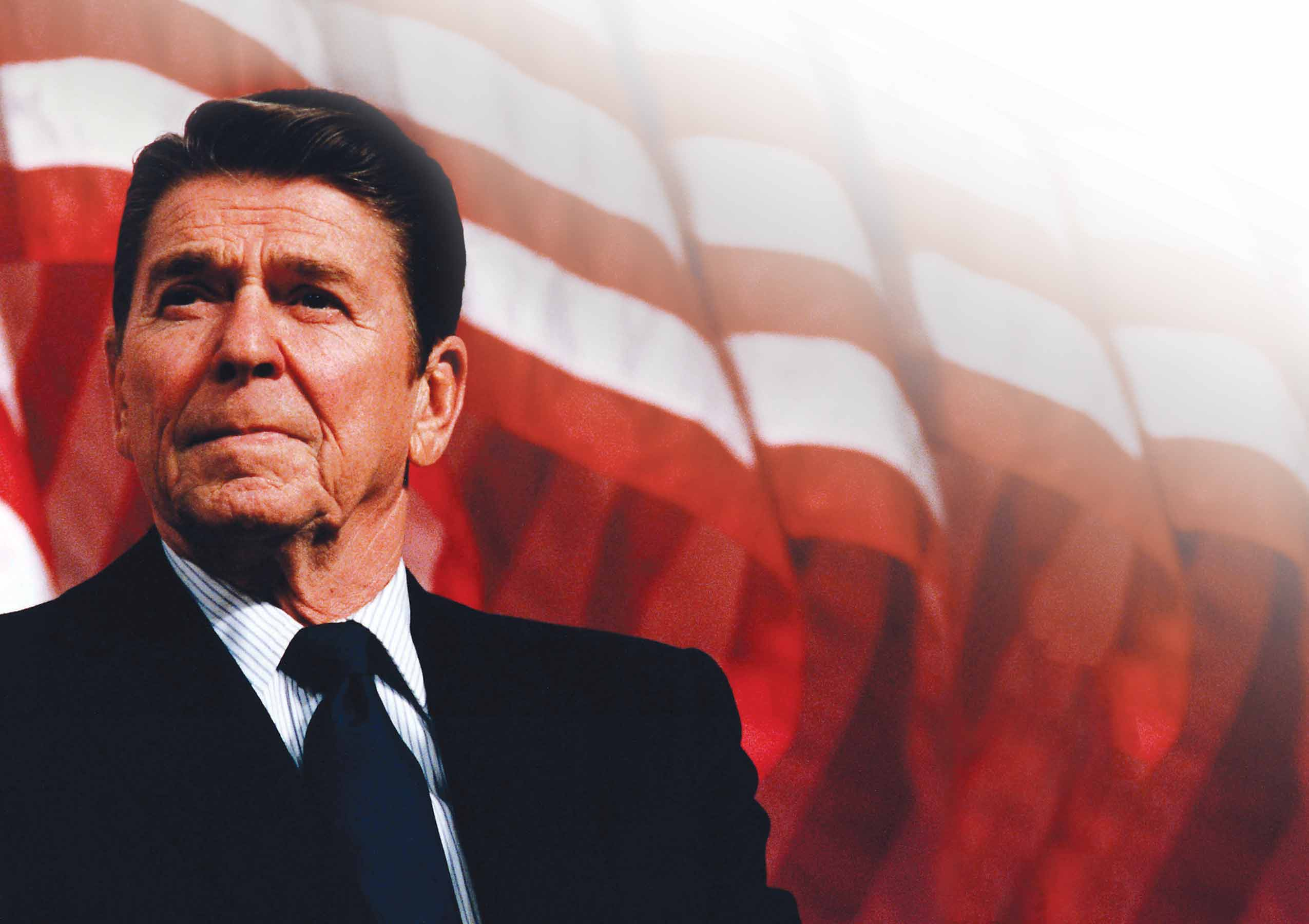 President Ronald Reagan looking thoughtfully into the distance, with American flag flying in background