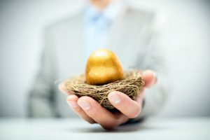 Businessman holding out nest with golden egg