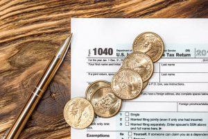1040 tax form and gold coins on wooden table