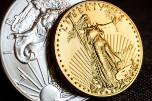 Silver American Eagle Coin and Gold American Eagle Coin on black background
