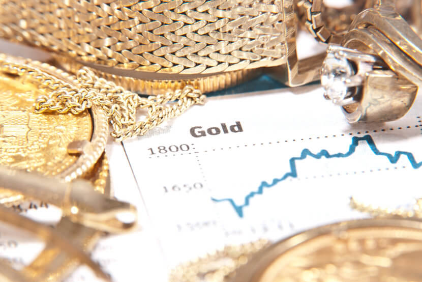 Gold chart surrounded by gold coins and jewelry