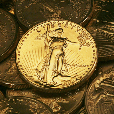 A 1 oz. Gold American Eagle Coin on top of other Gold American Eagle Coins