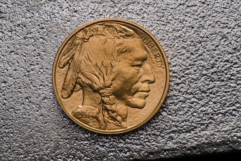 Indian head on Gold American Buffalo Coin against silver backdrop