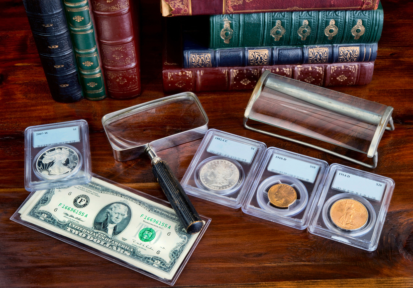Gold and silver coins in protective slabs on wooden table with money and magnifying glass