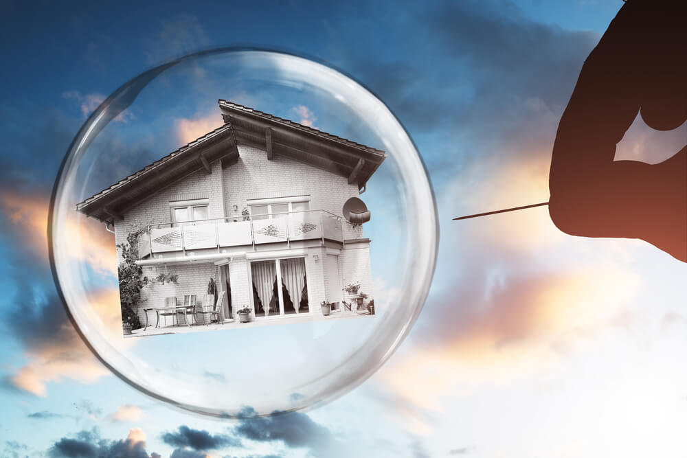 Human hand poling house and bubble with needle against cloudy sky