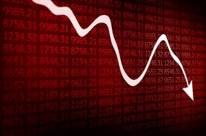 Stock market arrow graph going down on red display