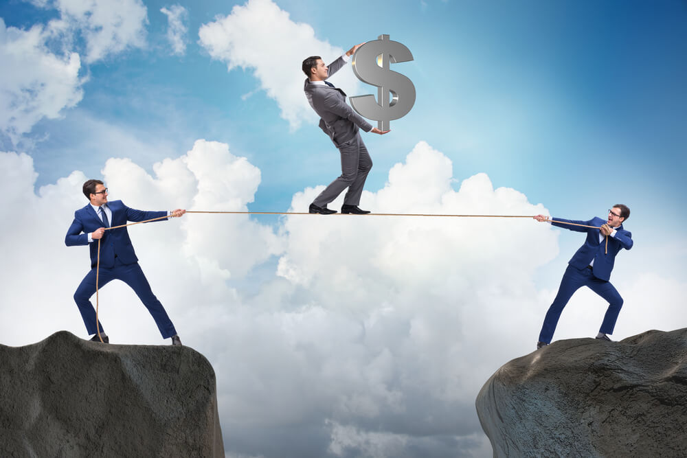 Businessman walking on tight rope holding a dollar sign