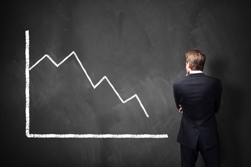 Business man looking at black and white decreasing chart on blackboard