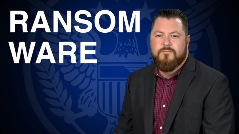 patrick brunson presenting on ransom ware dangers in front of blue background with u.s. seal