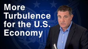 "Coy Wells presenting in front of a blue backdrop that says ""More Turbulence for the U.S. Economy"""