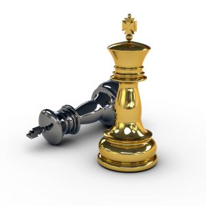 Gold and silver chess pieces with silver chess piece on the ground
