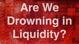 blurred red background of American dollar bill with white text in front that reads 'are we drowning in liquidity?'