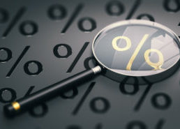 Magnifying Glass Laying on Top of Percentage Symbols