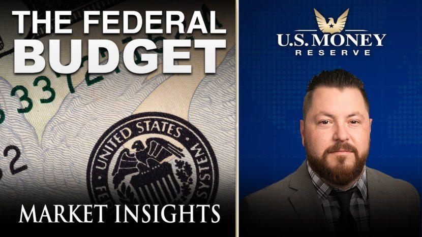 patrick brunson presenting next to an enlarged dollar bill regarding the federal budget