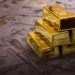Gold Bars Stacked on Top of One Hundred Dollar Bills