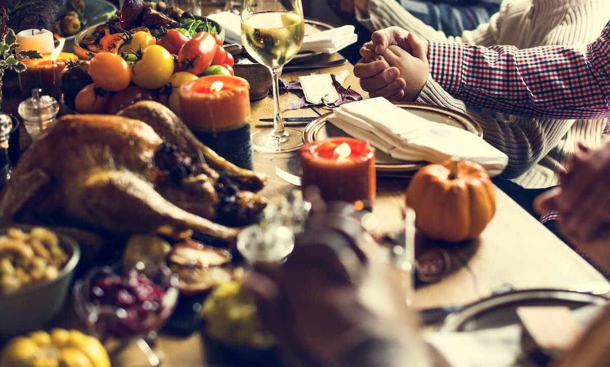 Thanksgiving table with people holding hands