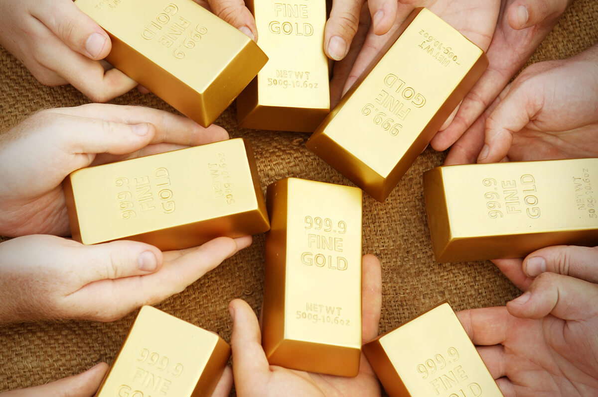 Multiple Hands Holding Gold Bars