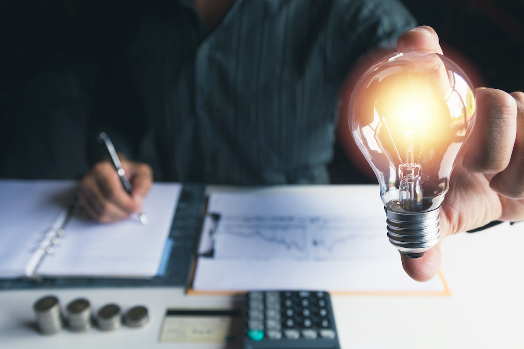 Person Writing in Notebook Holding Lit Lightbulb