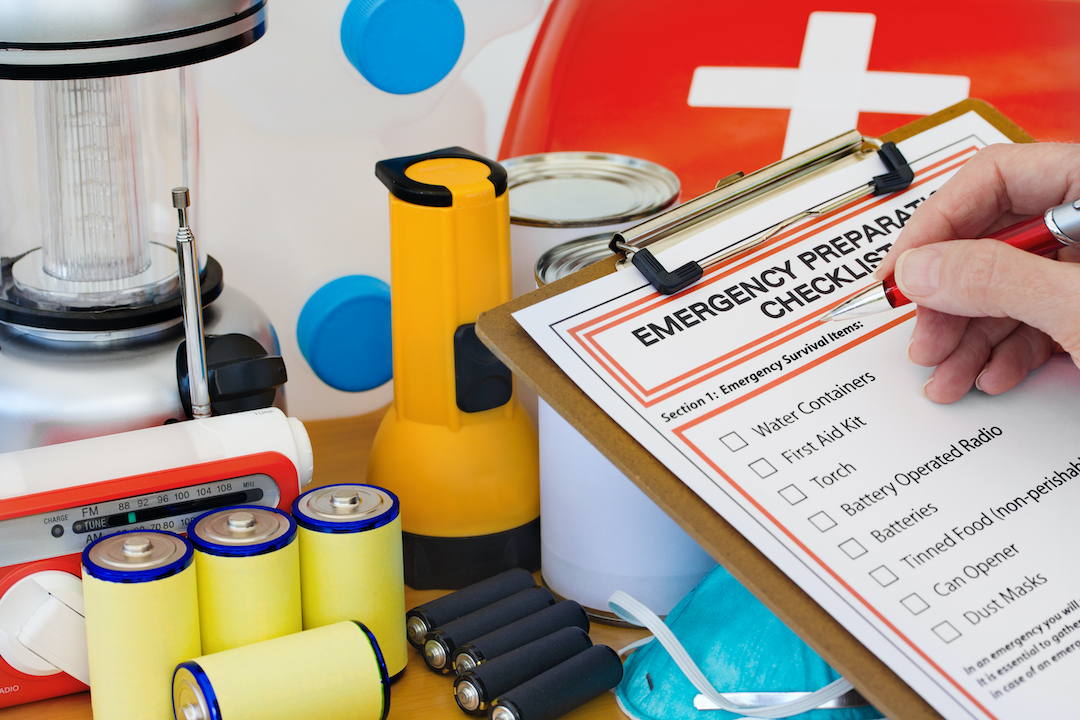 Person reviewing emergency preparedness checklist and looking at batteries, flashlight and first aid kit