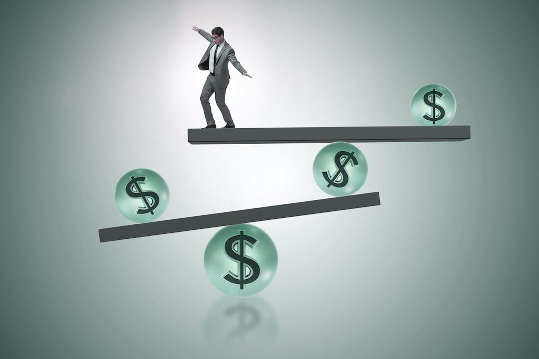 Man balancing on dollar signs