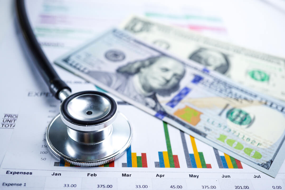 Stethoscope and U.S. dollars on charts and research data