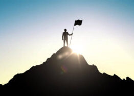 Man standing victorious atop a mountain