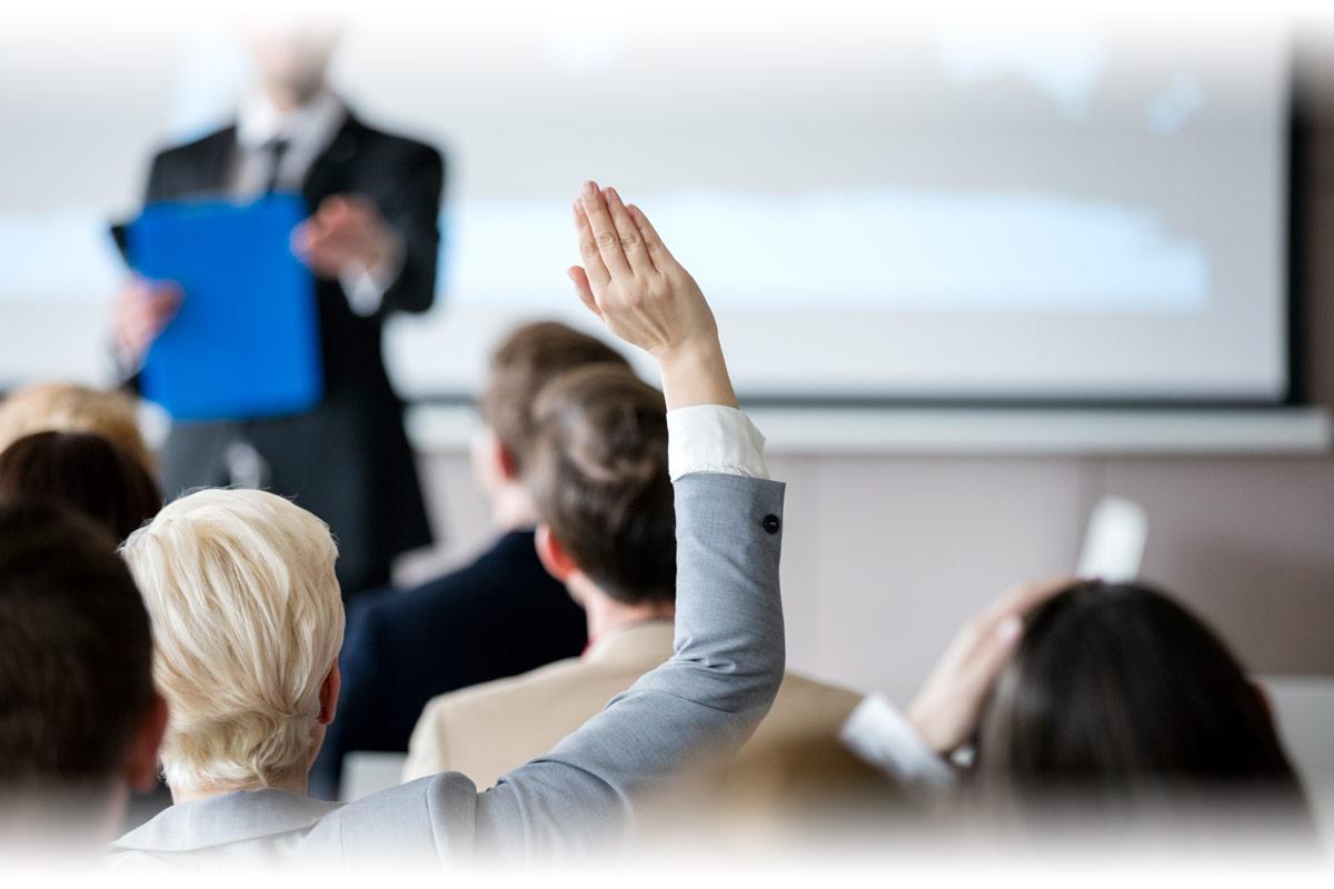 Woman raising hand during seminar