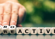 Hand turns dice and changes the word reactive to proactive.