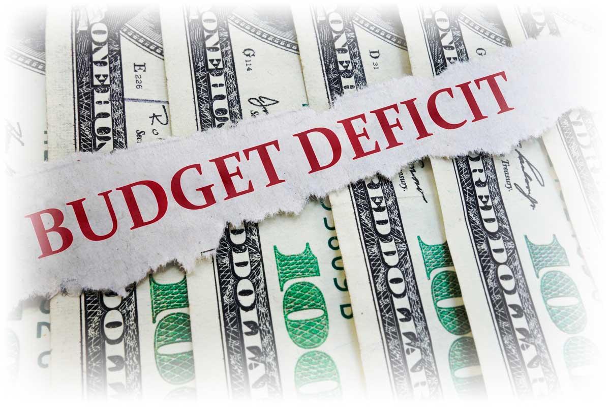 Scrap of paper reading BUDGET DEFICIT over row of $100 bills